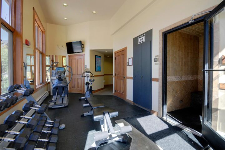 Versatile workout room with adjacent steam room.