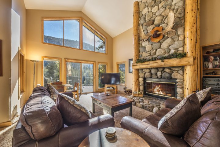Living room with 2-story stone fireplace