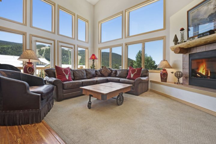 Living room with high windows framing the ski runs