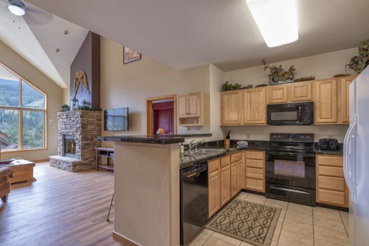 Kitchen with all major appliances, microwave, automatic coffee maker, and cooking supplies.