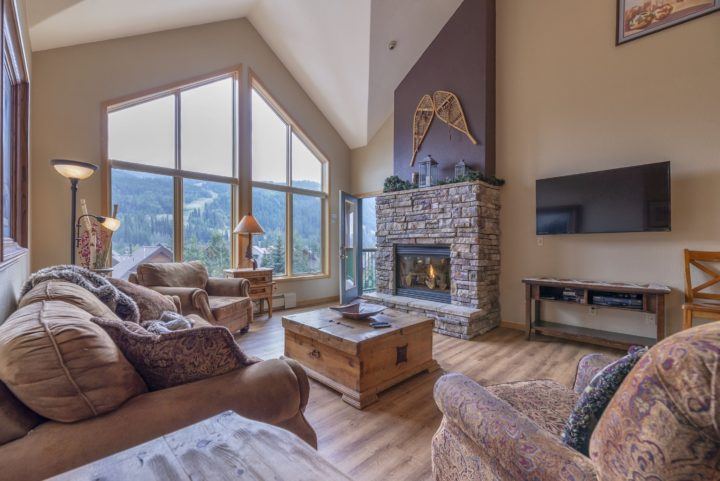 Main living area with stone fireplace, flat screen TV, and Queen fold out sofa.