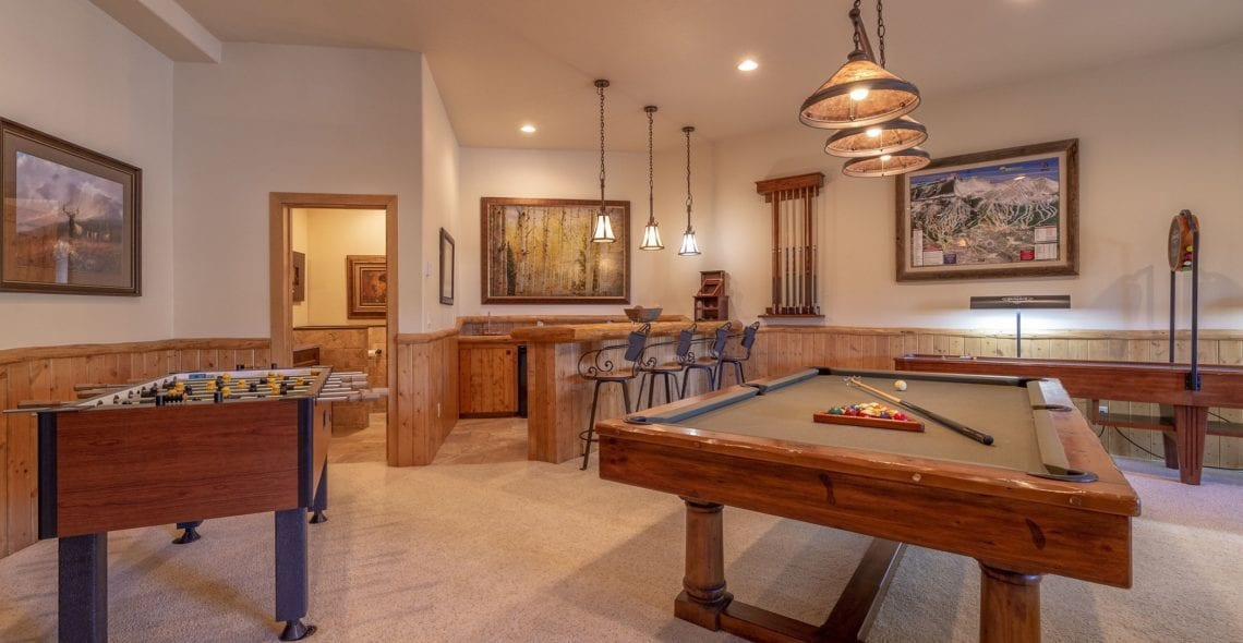 Pool table, foosball, shuffleboard table, and wet bar.
