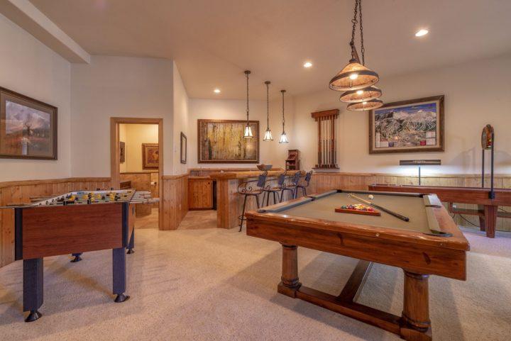 Pool table, foosball, shuffleboard table, and wet bar.