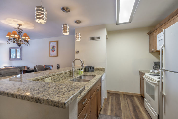 Newly renovated kitchen with wood flooring and granite counters.