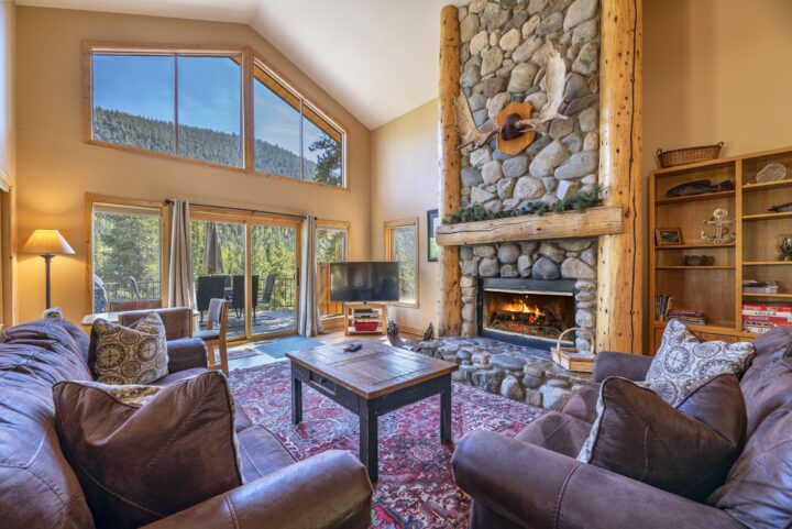 """Great Room area with stone fireplace, 55"""" TV, and private deck."""